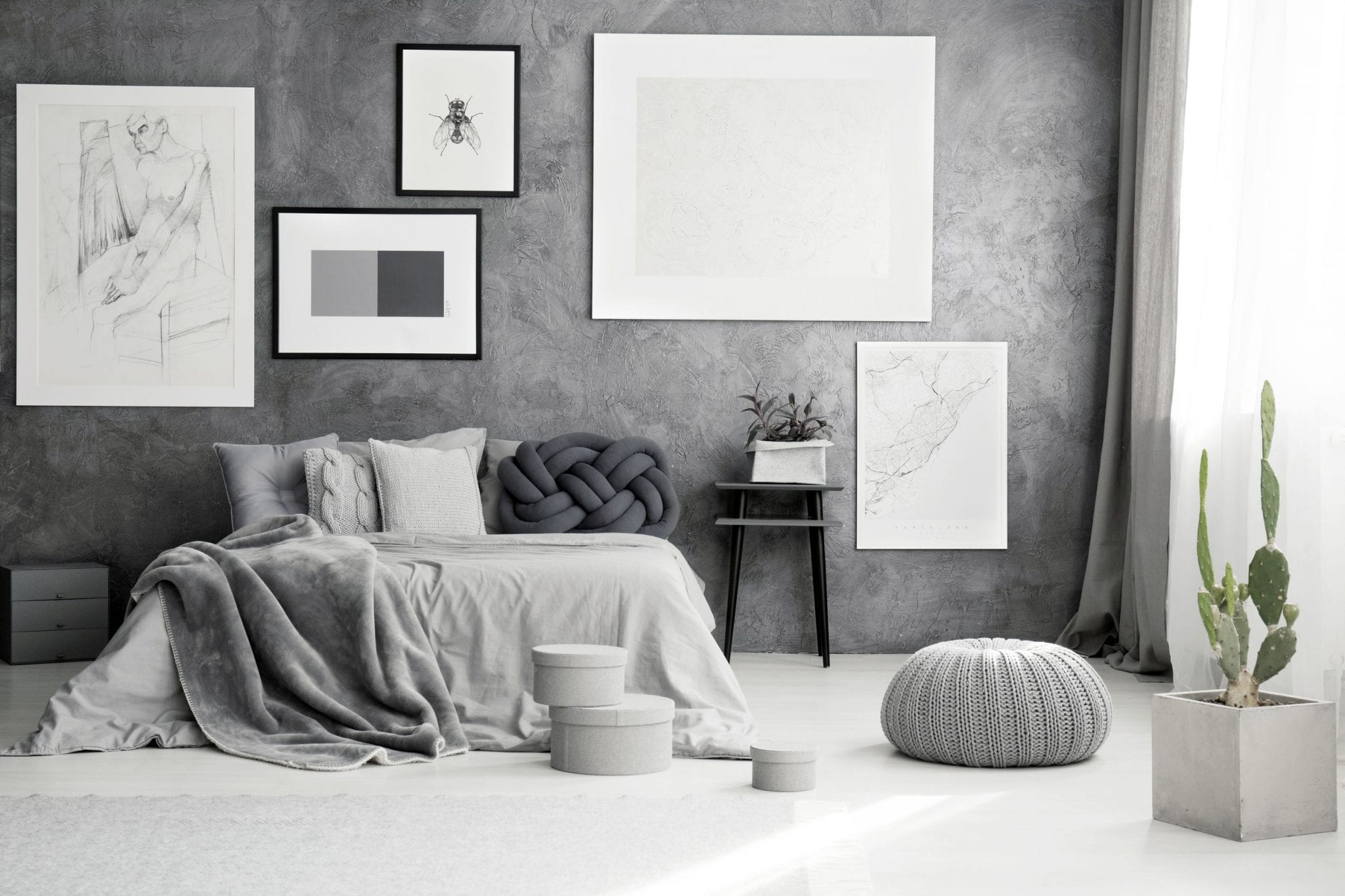 Cactus and pouf near king size bed with grey blanket in bedroom with gallery of posters on concrete wall